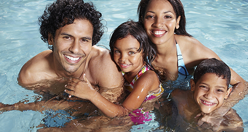 Parents and kids in swimming pool. Parents, find out how you can help improve school swimming.