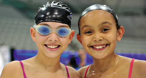 Two smiling girls by pool. Get involved with the ASA School Swimming campaign and help improve the quality of their lessons.