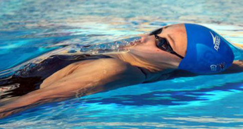 Woman in backstroke race. Improve your backstroke with our backstroke basics and drills.