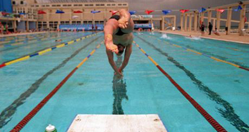 Swimmer diving off the block. Learn how to be the first swimmer off the block with Swimmers' Tips.