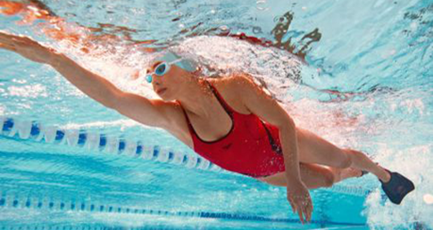 Woman swimming using fin. Learn how to use a fin to improve your swimming technique with our swimming tips.