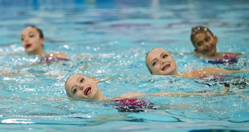 Young synchronised swimmers performing a routine. Get started with synchro.