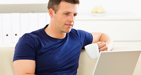 Man in blue t-shirt sat down looking at a Mac laptop. Welcome to the Support Services forum page.