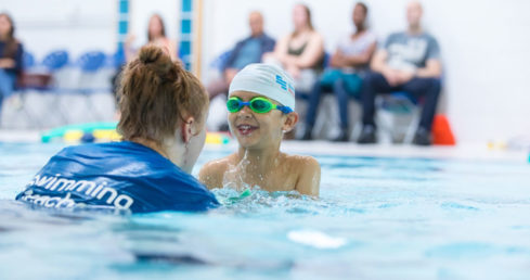 An image of a swimming teacher working 1-2-1 with a child on the Swim England Educator Licence page