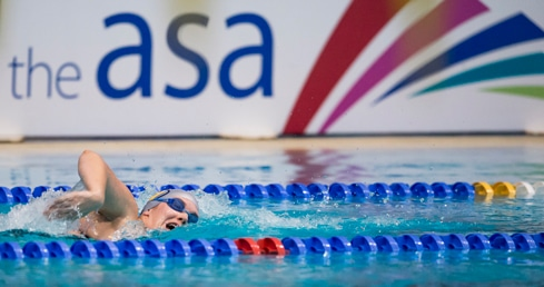 Top swimmers secure 2015 Winter Meet Qualifying Times. Swimmer in front of ASA branding