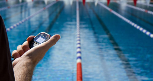 Online coach pass application for ASA National Championships. Picture of coach with stopwatch poolside.