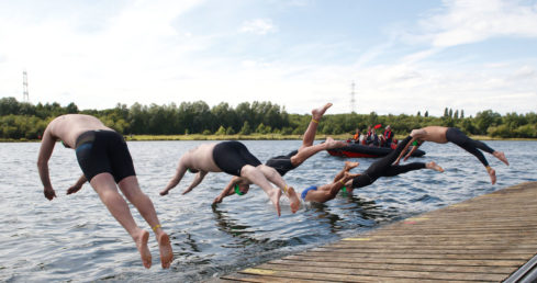 Image of Masters swimmers diving in to race at the Open Water Festival