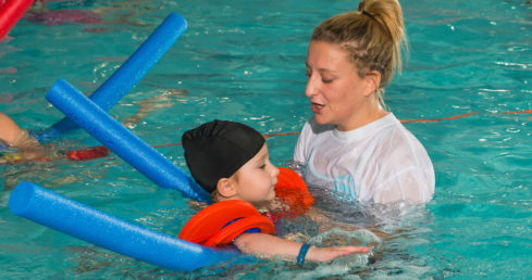 Swimming teacher with child. Used for page about licence renewals.