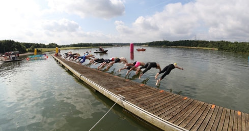 Swimmers diving into a lake in wetsuits