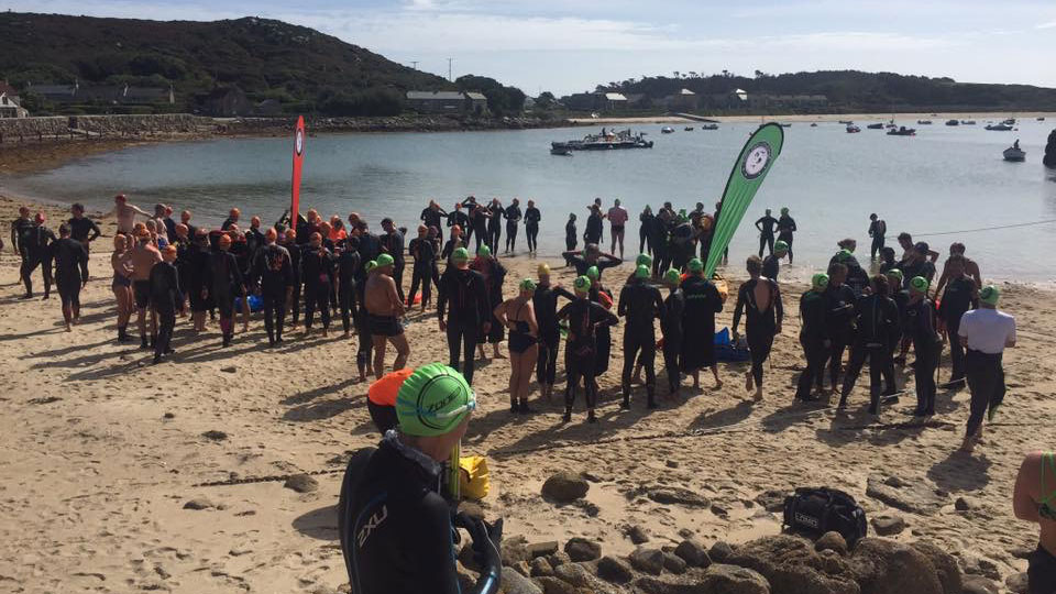 A beach with swimmers on it at the Scilly Sea Swim.
