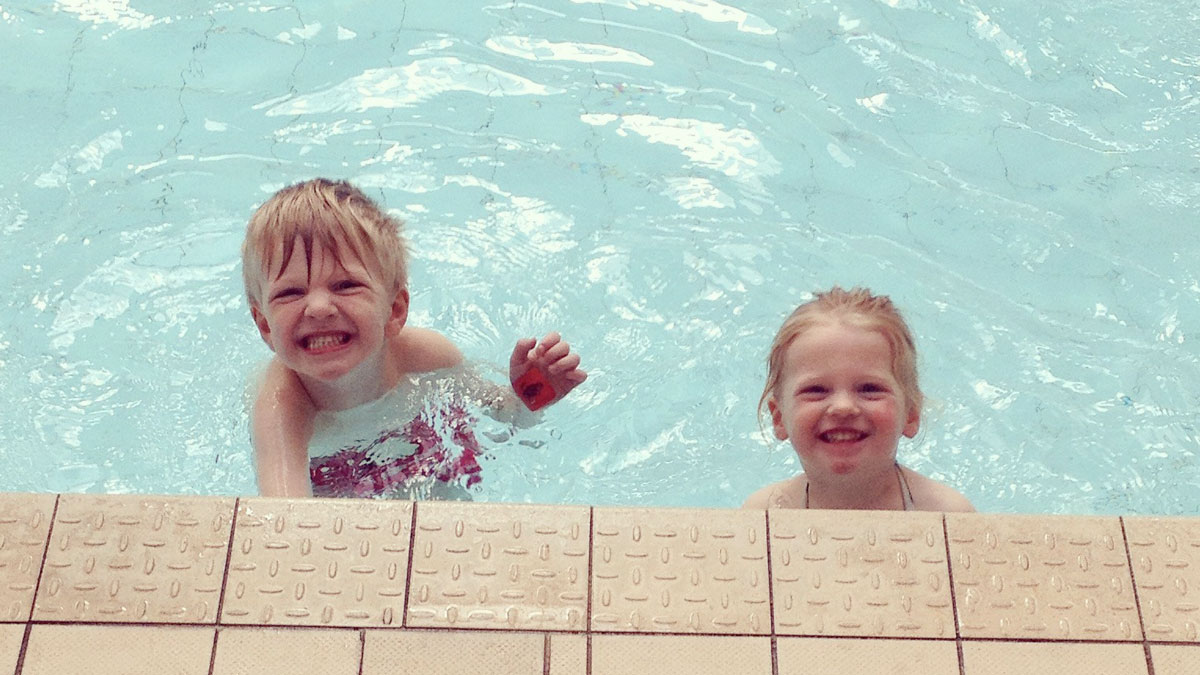 Two children smiling in the water. Taken from the Spirited Paddle Jumper's blog.