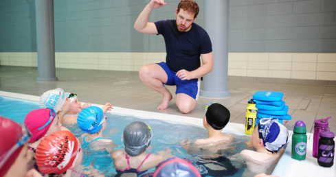 Swimming teacher with kids in the pool