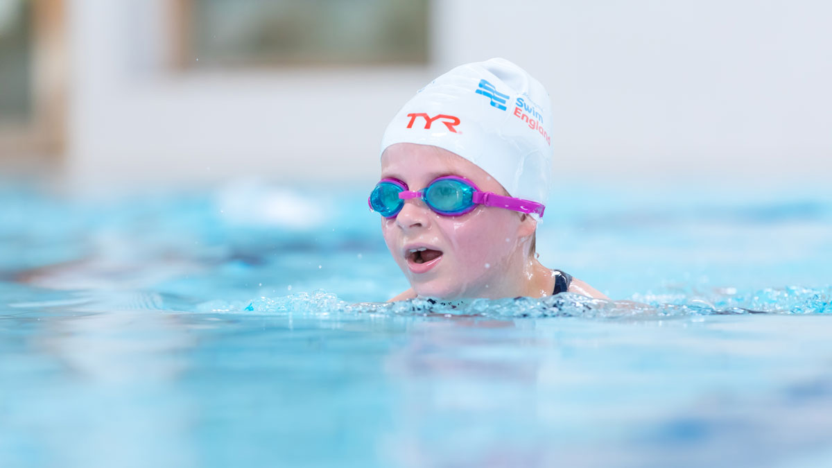 Girl learning to swim breaststroke. Learn to Swim lesson. Wearing Tyr and Swim England swimming cap.