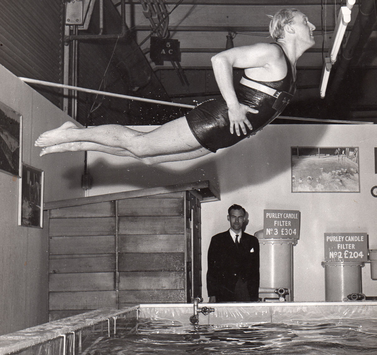 Trevor Baylis performing a swimming stunt. Taken from the May 2015 edition of the Swimming Times magazine.