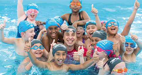 Swimming teacher in pool surrounded by happy kids. Be a school swimming Champion for the kids in your school.