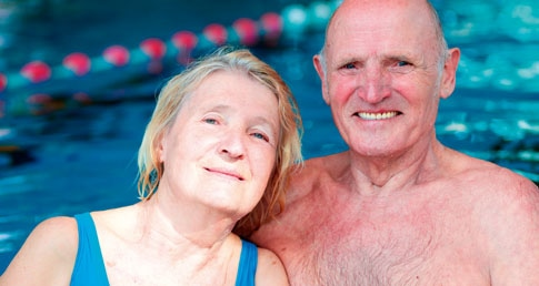 Older man and woman by pool. Find out about the ASA's Dementia Friendly Swimming Project