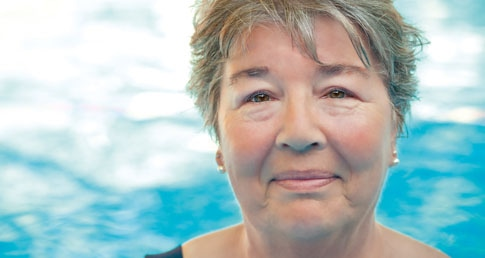 Older woman by pool. Find out about the aims of the Dementia Friendly Swimming Project