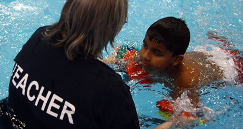 Female swimming teacher with young swimmer. About Swim England Workforce Support Services.