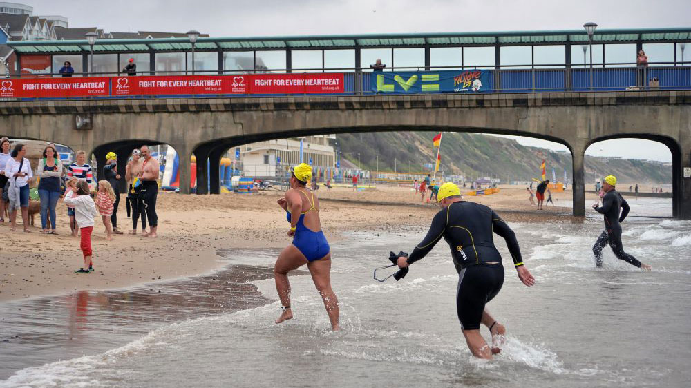 Swimmers running to the Bournemouth pier