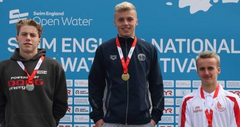 Swimmers standing on outdoor podium receiving medals