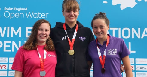 Female swimmers standing with medals on the podium