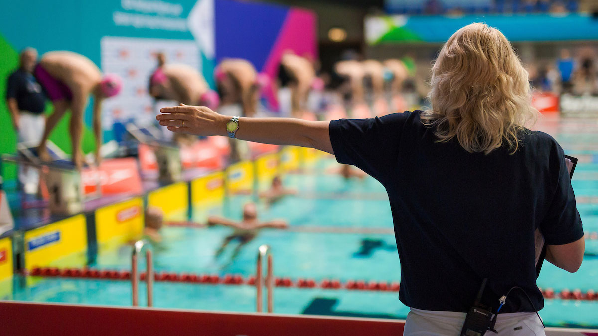 An official holds her arm out while swimmers are on the starting blocks.