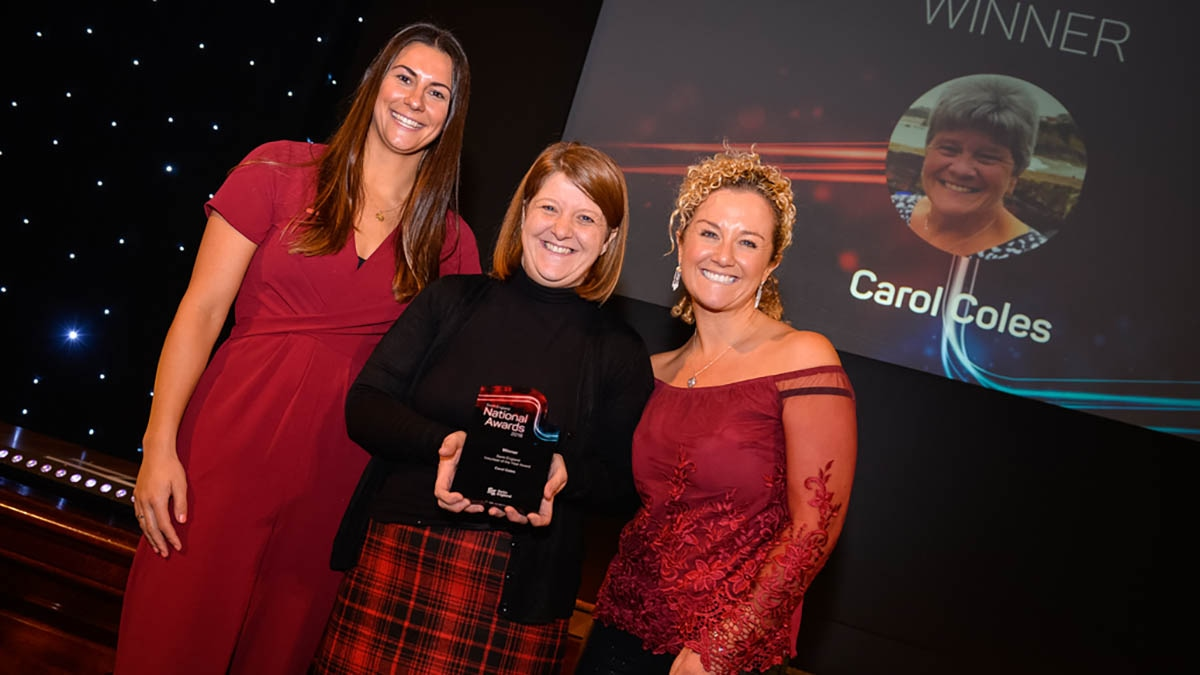 Ali Beckman and Stacey Cregeen received the Swim England Volunteer of the Year award on behalf of their mother, Carol Coles, from Aimee Willmott