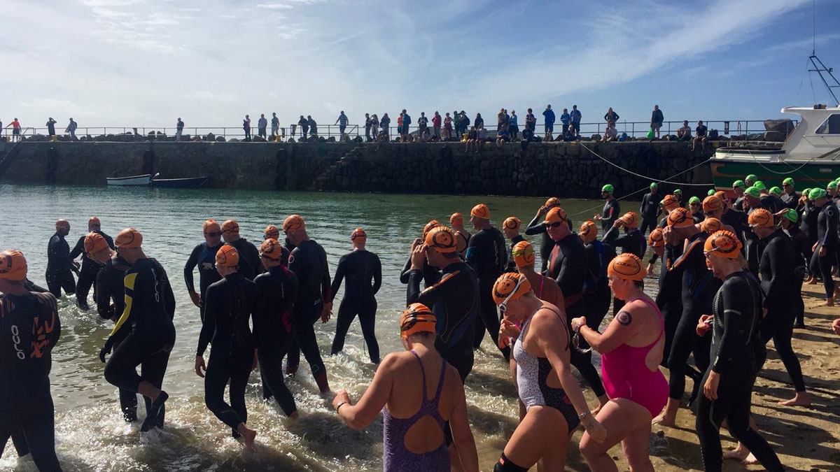 Swimmers going over pebbles as they enter the sea.