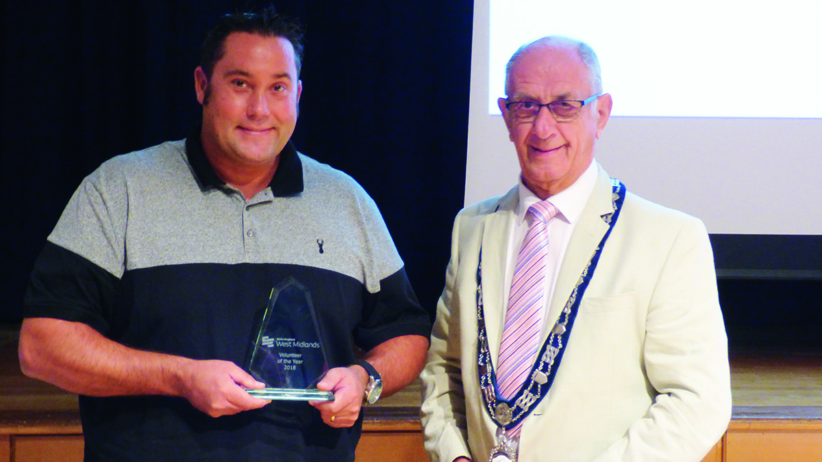 Craig Day receives the Swim England West Midlands region volunteer of the year award from regional president David Corbett