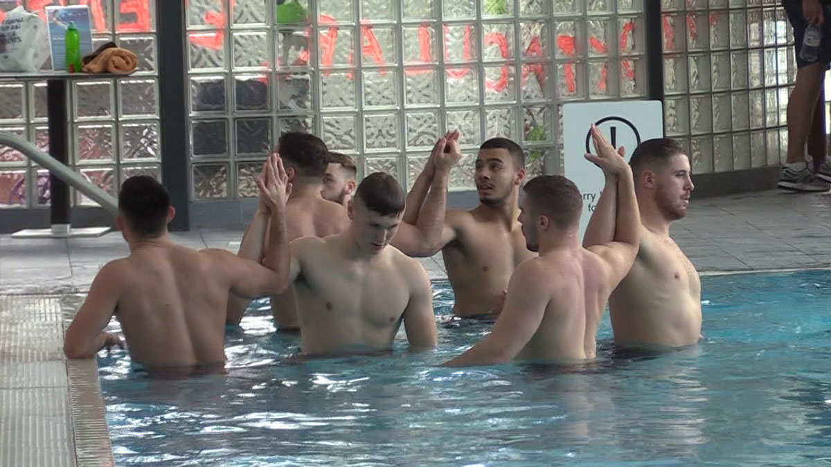 Rugby league players stretching in the pool