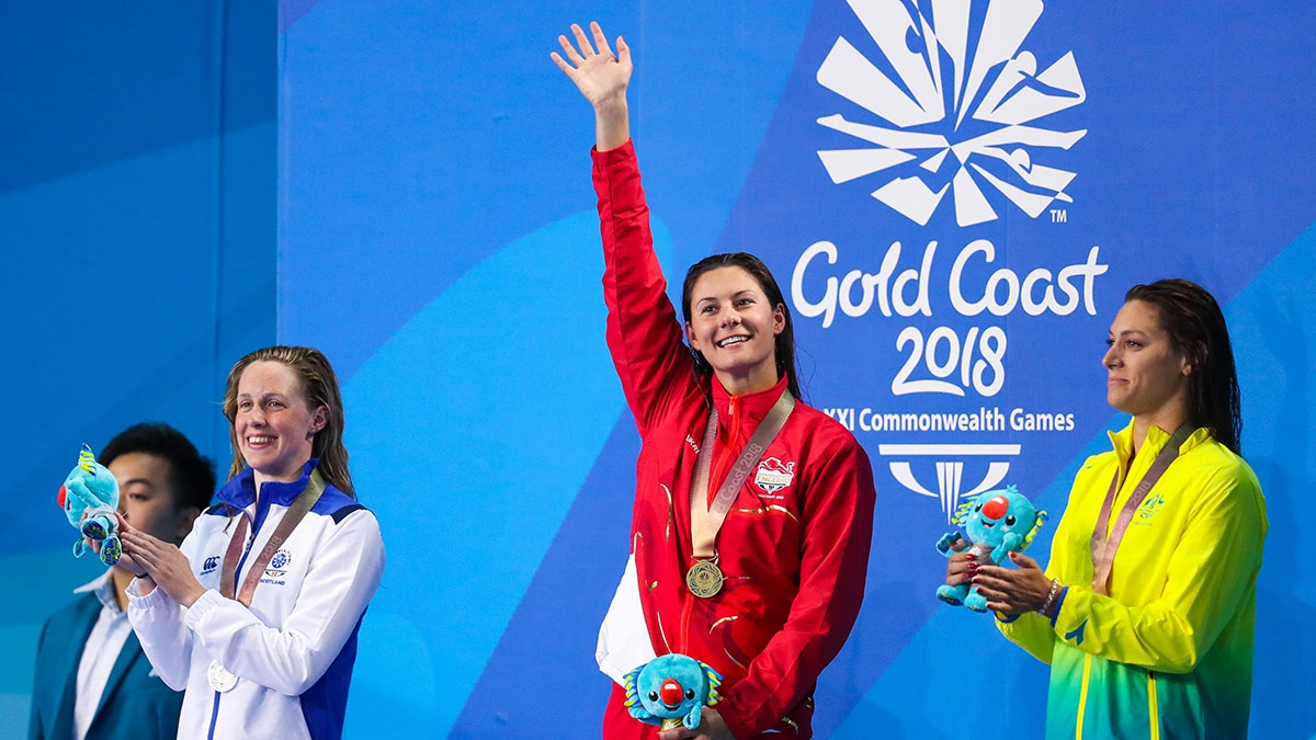 Aimee Willmott waves to the crowd as she stands on top of the podium at the 2018 Commonwealth Games