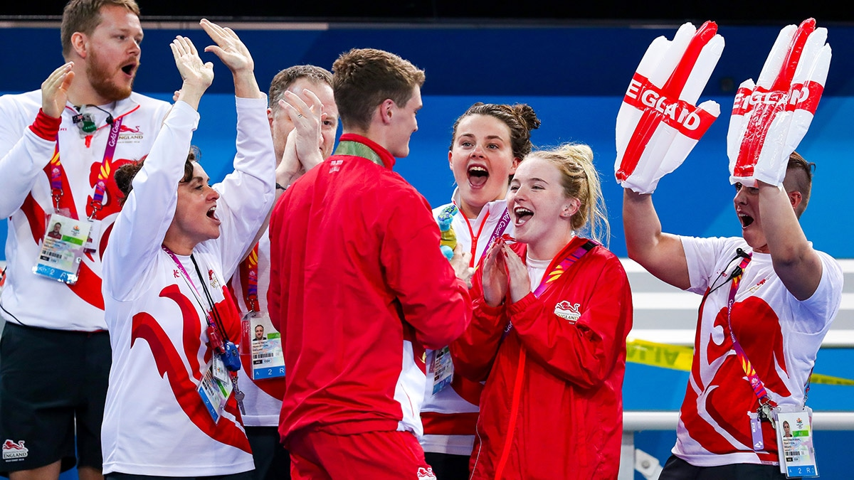 James Wilby celebrates his 200m Breaststroke victory at the 2018 Commonwealth Games with his Team England colleagues