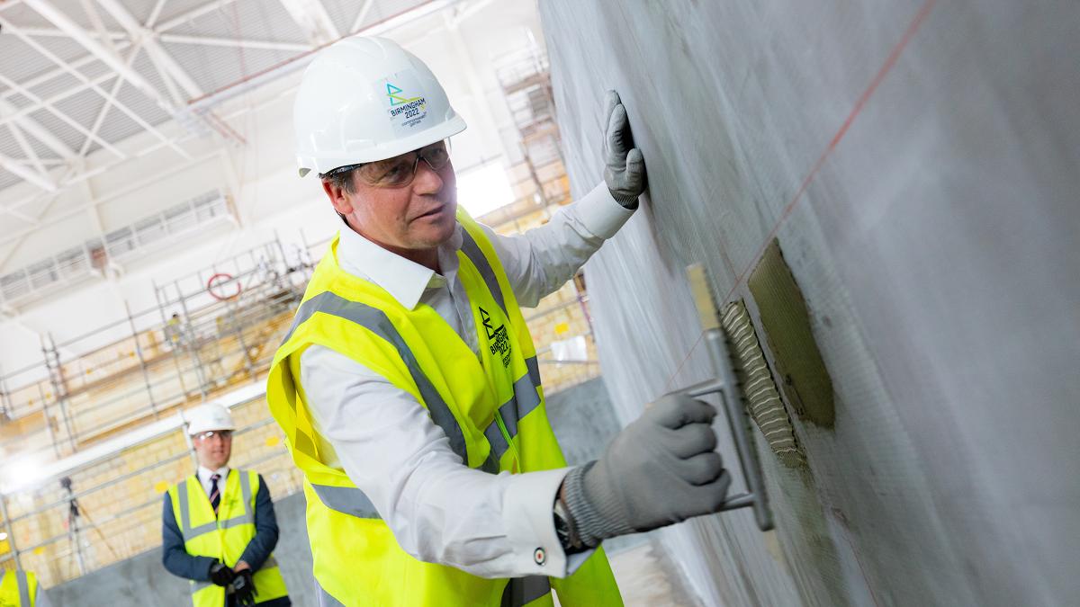 Minister for Sport Nigel Huddleston laying a tile at Sandwell Aquatics Centre